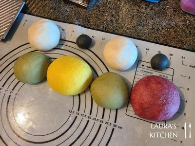 两个10g面团用手混入少许竹炭粉,两个120g面团混入适量抹茶粉,两个250g面团分别混入红麴粉和姜黄粉,比较大的面团可以用搅拌机打,大约打个5分钟就会均匀了。 染色完成后,将每一个面团滚圆。 白色面团因为不需染色闲置最久,记得把面团内的空气压掉,以免造成面团发酵程度不一