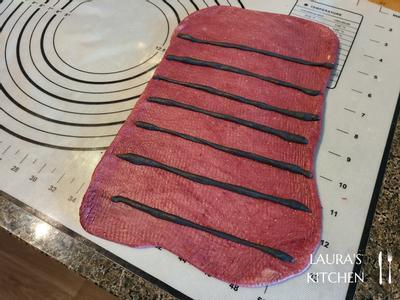 将红色/黄色面团擀成长方形,依序放入黑色长条,再将面团由下方往上卷起。 猜到了吗,没错,黑黑的就是西瓜籽!